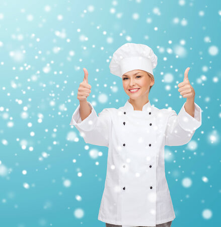 thumps up: christmas, cooking, profession, gesture and people concept - smiling female chef showing thumps up over blue snowy background