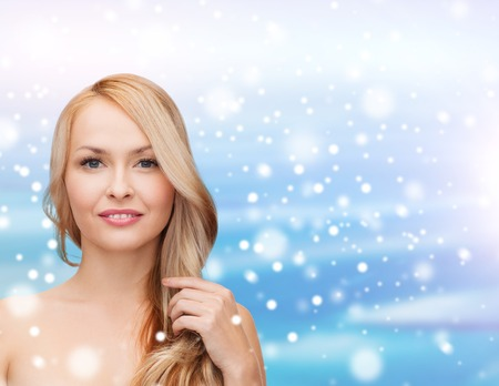 heath, people, haircare and beauty concept - beautiful young woman with bare shoulders touching her hair over blue sky, snow and clouds