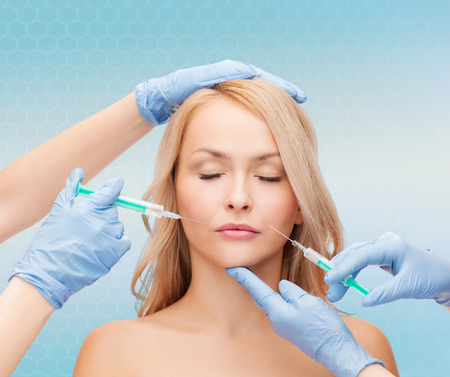 beautician: beauty, people and plastic surgery concept - woman face and beautician hands with syringes Stock Photo