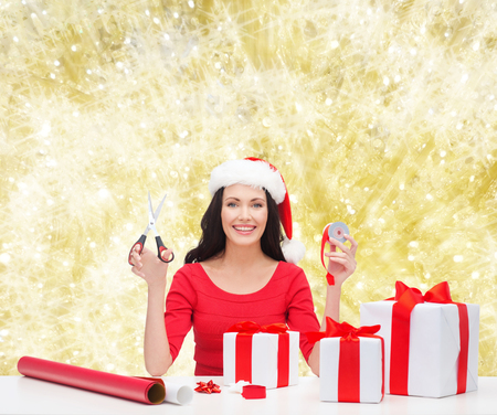 christmas, holidays, celebration, decoration and people concept - smiling woman in santa helper hat with scissors packing gift boxes over yellow lights  photo
