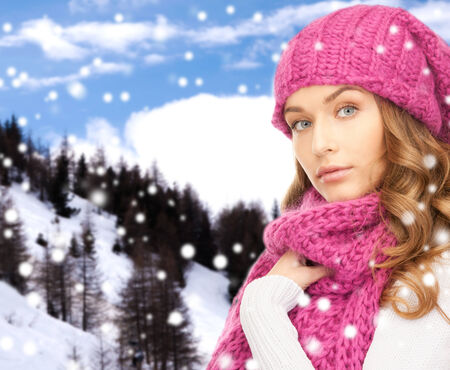 pink hat: happiness, winter holidays, christmas and people concept - young woman in pink hat and scarf over snowy mountains background
