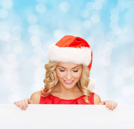 christmas, x-mas, people, advertisement and sale concept - happy woman in santa helper hat with blank white board over blue lights  photo