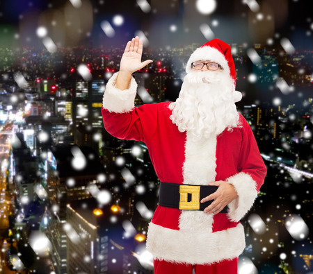 es: christmas, holidays, gesture and people concept - man in costume of santa claus waving hand over snowy night city