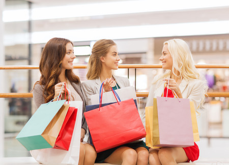 sale, consumerism and people concept - happy young women with shopping bags in mall Stockfoto