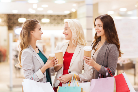 consumerism: sale, consumerism and people concept - happy young women with shopping bags and coffee paper cup in mall