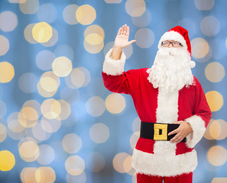 christmas, holidays, gesture and people concept - man in costume of santa claus waving hand over blue lights  photo