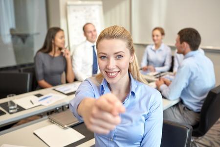 het bedrijfsleven, mensen en teamwork concept - lachende zakenvrouw wijzende vinger omhoog met de groep van ondernemers bijeenkomst in kantoor