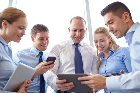 zakelijk, Teamwork, mensen en technologie concept - business team met tablet pc's en smartphones bijeenkomst in het kantoor Stockfoto