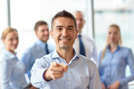 business, people, gesture and teamwork concept - smiling businessman pointing finger to you with group of businesspeople meeting in office photo