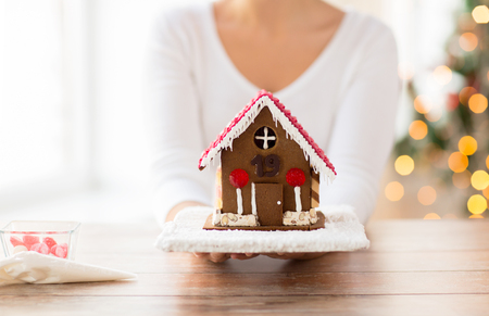 sugarcoated: cooking, people, christmas and baking concept - close up of happy woman holding and showing gingerbread house at home