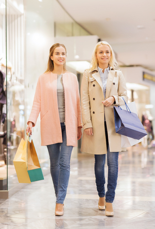 sale, consumerism and people concept - happy young women with shopping bags walking in mall photo