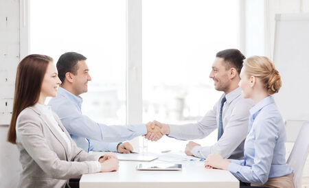 technology deal: business and office concept - smiling business team having meeting in office