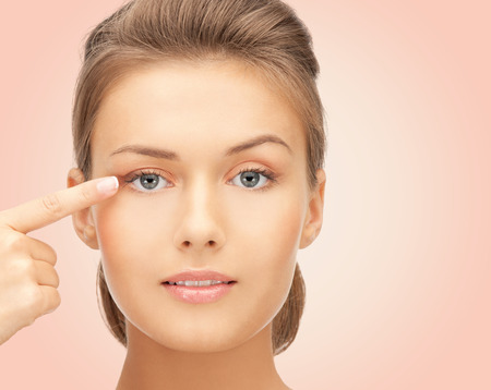 eyelid: beauty, people and health concept - beautiful young woman pointing finger to her eye over pink background