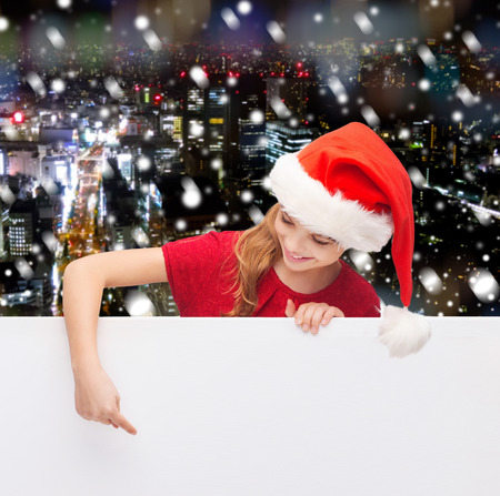 christmas, holidays and advertisement concept - happy girl in santa helper hat pointing finger on blank white board over snowy night city background photo