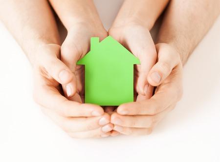 viviendas: bienes ra�ces y el concepto de hogar - foto de primer plano de las manos masculinas y femeninas, sosteniendo verde casa de papel en blanco Foto de archivo