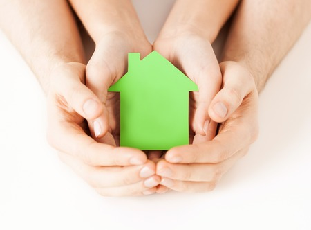 small home: real estate and family home concept - closeup picture of male and female hands holding green blank paper house Stock Photo