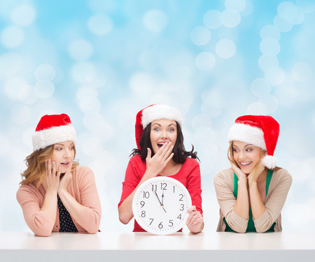 christmas, winter, holidays, time and people concept - smiling women in santa helper hats with clock over blue lights