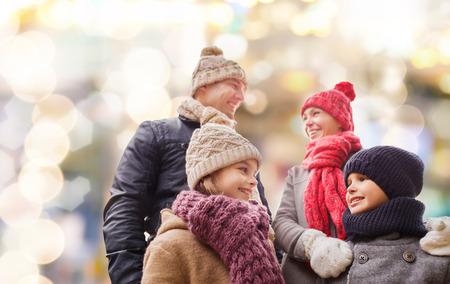 estado del tiempo: la familia, la infancia, la estaci�n, d�as de fiesta y la gente - concepto de familia feliz en ropa de invierno sobre fondo de las luces