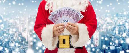 christmas profits: christmas, holidays, winning, currency and people concept - close up of santa claus with euro money over snowy city background