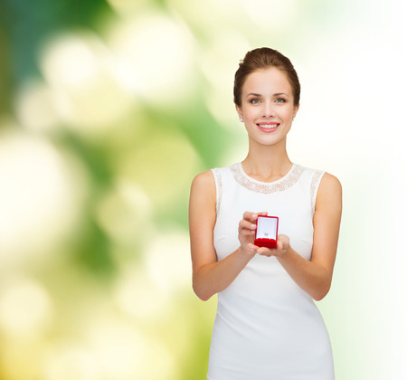 wedding, love, engagement and people concept - smiling woman in white dress holding red gift box with diamond ring over green background photo