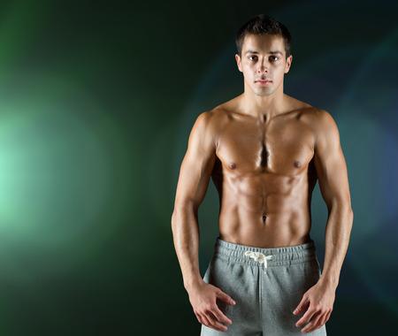nackte brust: Sport, Bodybuilding, Kraft und Menschen Konzept - junger Mann mit nackten muskulösen Oberkörper stehend auf einem dunklen Hintergrund