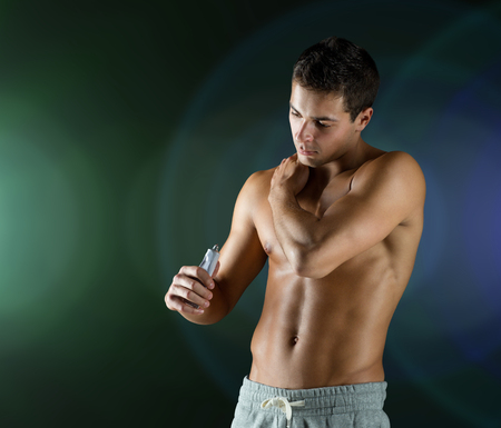 male torso: sport, bodybuilding, medicine and people concept - young man applying pain relief gel on his shoulder over dark background