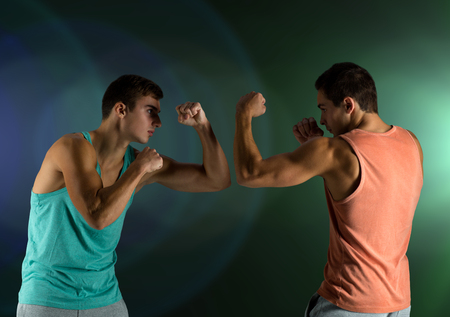 sport, competition, strength and people concept - young men fighting hand-to-hand over dark  Stock Photo