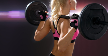 body pump: fitness, sport and dieting concept - sporty woman exercising with barbell from back Stock Photo