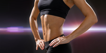 six packs: fitness and diet concept - close up of beautiful athletic female abs in sportswear