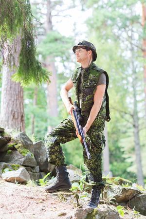 fusil de chasse: la chasse, la guerre, l'armée et le peuple notion - jeune soldat, ranger ou le chasseur avec un pistolet dans la forêt