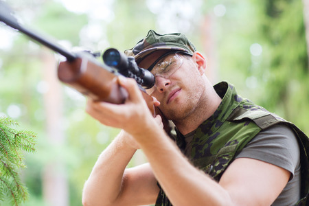 hunting rifle: hunting, war, army and people concept - young soldier, ranger or hunter with gun aiming and shooting in forest