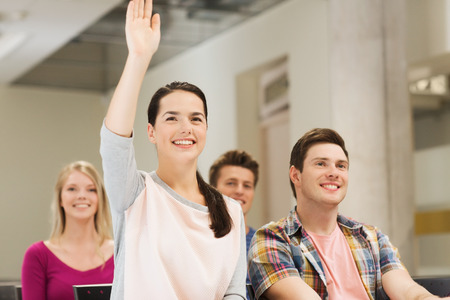 hand raising: education, high school, teamwork and people concept - group of smiling students raising hand in lecture hall