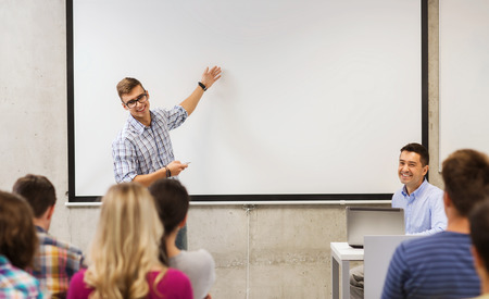 education, high school, technology and people concept - student standing with remote control, laptop computer in front of teacher and classmates in classroom Stock Photo