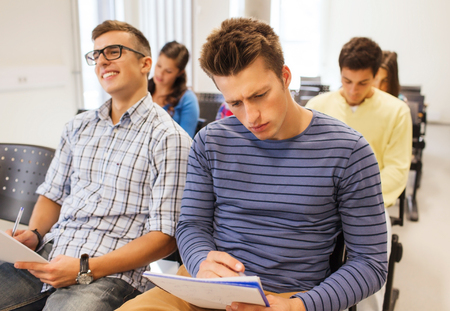 education, high school, teamwork and people concept - group of smiling students with notepads sitting in lecture hall photo