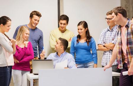 maestra ense�ando: la educaci�n, la escuela secundaria, la tecnolog�a y concepto de la gente - grupo de estudiantes sonrientes y profesor de papeles, ordenador port�til en el aula Foto de archivo