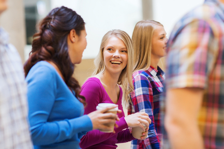 education, high school, friendship, drinks and people concept - group of smiling students with paper coffee cups Stock Photo