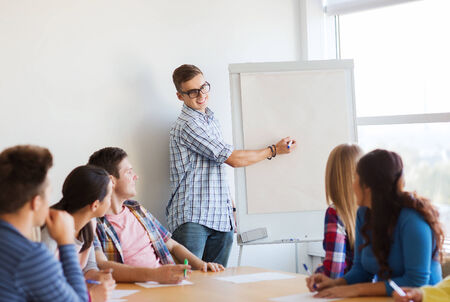 education, teamwork and people concept - smiling students with white board sitting an table indoors Stock Photo