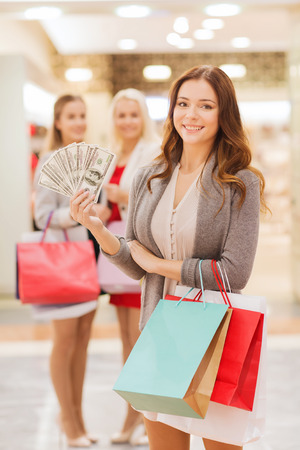 consumerism: sale, consumerism and people concept - happy young women with shopping bags and dollar cash money in mall