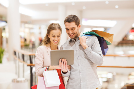 shopping center: sale, consumerism, technology and people concept - happy young couple with shopping bags and tablet pc computer pointing finger in mall