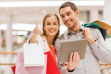 woman shopping: sale, consumerism, technology and people concept - happy young couple with shopping bags and tablet pc computer pointing finger in mall
