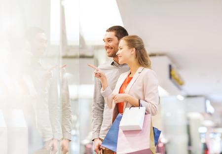 compras: venta, el consumismo y el concepto de la gente - joven pareja feliz con bolsas de la compra que señala el dedo para ir de compras en el centro comercial ventana