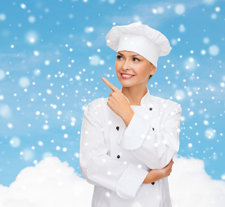 christmas cooking: christmas, cooking, holidays and people concept - smiling female chef, cook or baker pointing finger up over blue snowy sky and cloud