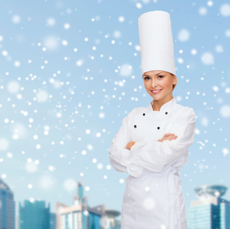 christmas cooking: christmas, cooking, holidays and people concept - smiling female chef, cook or baker dreaming over blue snowy sky and city background background
