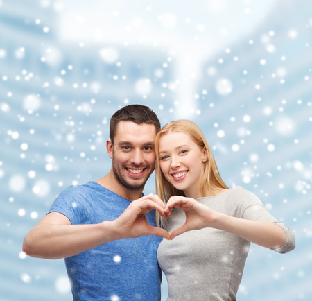 inlove: love, people and family concept - smiling couple making heart shape gesture hugging over snow and city buildings background