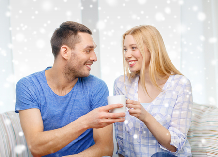 family couch: love, family, drinks and people concept - smiling couple with cup of tea or coffee at home Stock Photo
