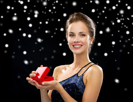 holidays, presents, luxury and happiness concept - smiling woman in dress holding red gift box over black snowy background photo