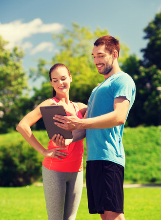 internet class: fitness, sport, friendship, technology and lifestyle concept - smiling couple with tablet pc computer outdoors