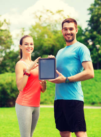 young add: fitness, sport, friendship, technology and lifestyle concept - smiling couple with tablet pc computer outdoors