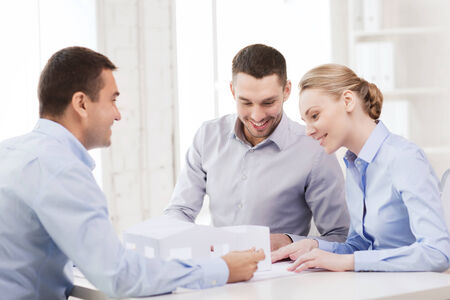 financial planner: home, design and architecture concept - couple looking at blueprint and model of their new house at office