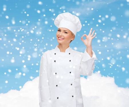 christmas cooking: christmas, cooking, profession, gesture and people concept - smiling female chef showing ok hand sign over blue snowy sky and cloud background